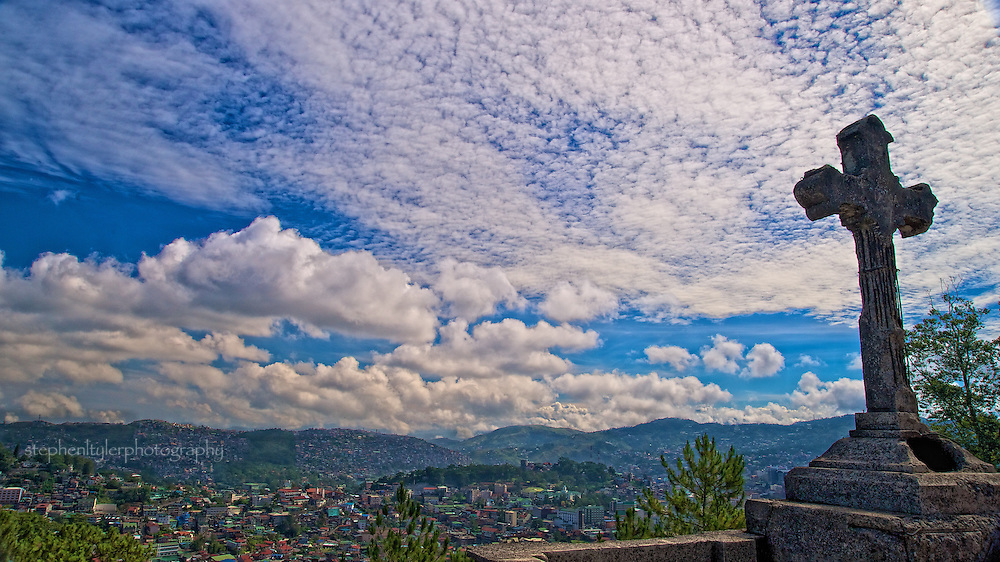 Panoramic view of the City of Baguio beneath the cross on the roof of the ongoing restoration work on Baguio Heritage Hill and Nature Park. Originally built in 1900 as part of the Dominican Order of the Philippines, it was used as a summer retreat house and later became the Collegio del Santissimo Rosario. During WWII, it was converted into a refuge center and bombed by the Japanese resulting in major devastation. Restoration was slow because of funding and spooky stories of ghost hauntings, until the City of Baguio took over ownership in 2004.