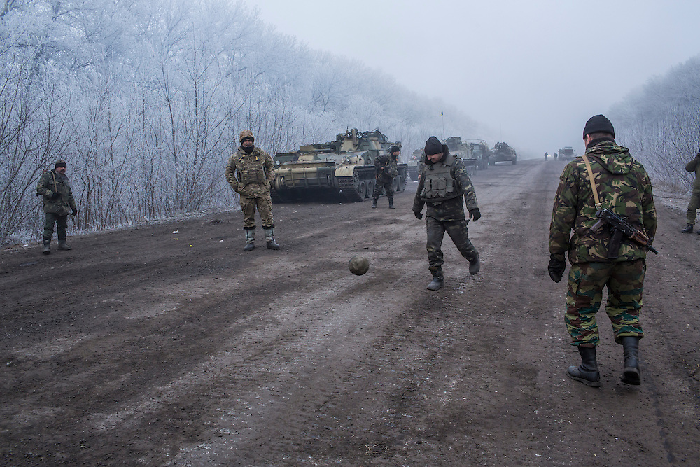 ARTEMIVSK, UKRAINE - FEBRUARY 15: Ukrainian soldiers play football on the road leading to the embattled town of Debaltseve on February 15, 2015 outside Artemivsk, Ukraine. A ceasefire scheduled to go into effect at midnight was reportedly observed along most of the front, save for near the embattled town of Debaltseve. (Photo by Brendan Hoffman/Getty Images) *** Local Caption ***