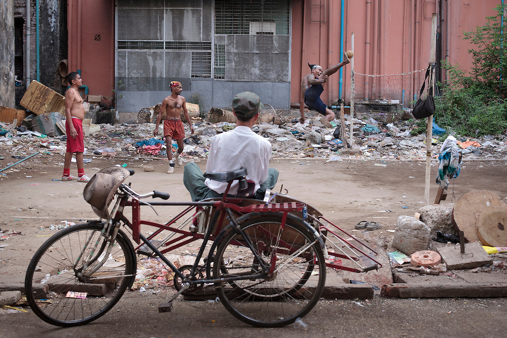 A chinlone (Burmese national sport) watch the match sitting on his rickshaw on a laneway in Yangon, Yangon division, Myanmar.