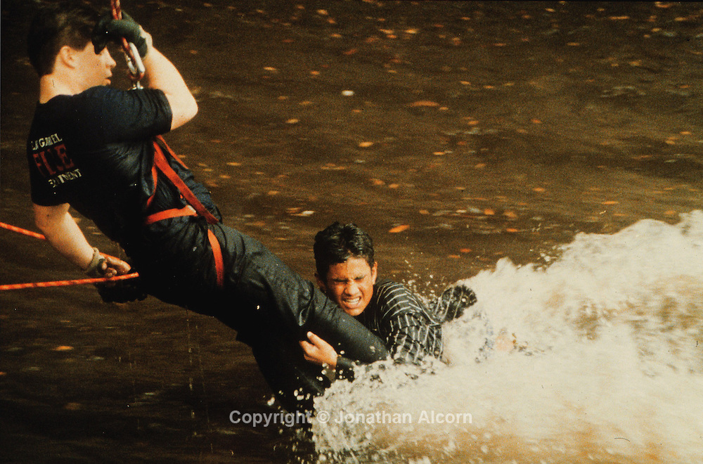 Firefighter attempts a swift water rescue. The victim slipped away, but was rescued downstream.