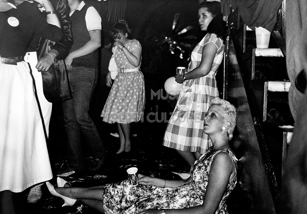 End of the night club scene, Rock n' Roll revival, one girl sitting on floor, one standing, drinking from Coke cups, UK, 1980's.