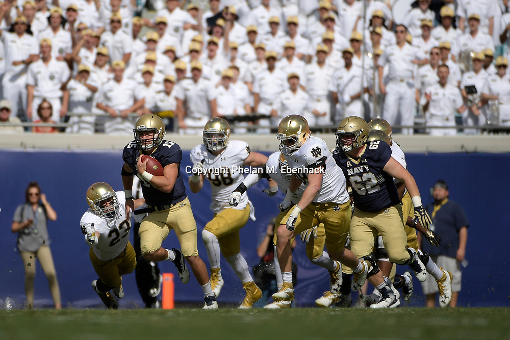 Navy quarterback Will Worth (15) rushes for a long gain past Notre Dame linebacker Greer Martini (48) and defensive lineman Andrew Trumbetti (98) during the first half of an NCAA college football game in Jacksonville, Fla., Saturday, Nov. 5, 2016. (Photo by Phelan M. Ebenhack)