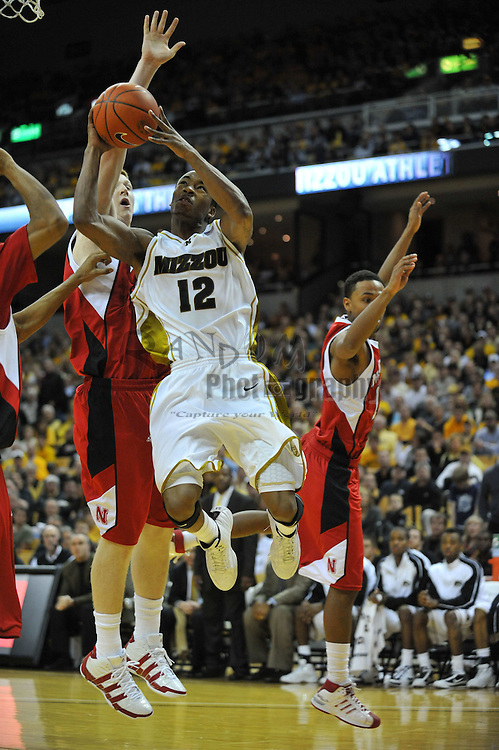 Jan 23, 2010; Columbia, MO, USA; Missouri Tigers guard Marcus Denmon (12) goes up for a shot and is fouled by Nebraska Cornhuskers guard Brandon Richardson (3) in the second half at Mizzou Arena in Columbia, MO. Missouri won 70-53. Mandatory Credit: Denny Medley-US PRESSWIRE