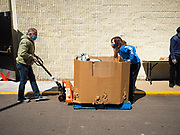 "11 MAY 2020 - DES MOINES, IOWA: RICHARD JESS and GRACE OSTRANDER move a pallet of food packages at a ""no touch"" emergency food pantry at DSM First Church in Des Moines. The emergency pantry at DSM First Church expanded from distribution one day a week to three days per week after the COVID-19 pandemic forced the closure of many Iowa businesses. Food banks and emergency pantries in Iowa continue to see increased demand for services, even though the governor is reopening the state's economy. Iowa's unemployment rate for April hasn't been released yet, but based on national trends, it is expected to soar to well over 10% from 3.8& in March. COVID-19 infections continue to skyrocket. On Monday, 11 May, the governor announced that 12,373 people tested positive for coronavirus (SAR-CoV-2) and  271 had died.             PHOTO BY JACK KURTZ"