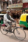 Indian man riding bicycle street scene in city of Varanasi, Benares, Northern India