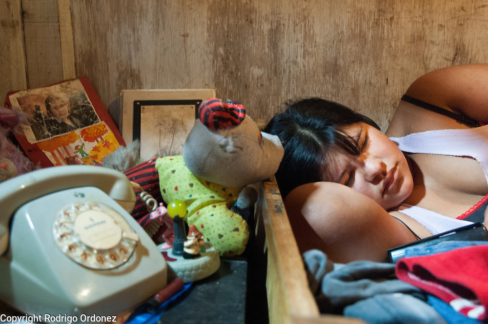 Noelia, 15, rests on her bed, next to toys, old photographs and a broken telephone. Noelia does not go to school.<br /> For most inhabitants of Ocho de Mayo, dignity is the main goal. Many who have had to live in the streets now focus their energies on providing a better life for their children. They all agree on the need of education to get jobs.