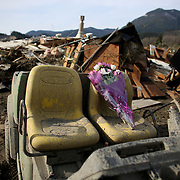 A bouquet of flowers left for the deceased sits perched on the seat of a damaged vehicle in the wreckage of homes and lives destroyed by a mudslide near Oso, Wash. In the wake of Saturday's mudslide on Highway 530 in Snohomish County, there have been 175 reports of missing people and the death toll has risen to 14. (Joshua Trujillo, seattlepi.com)