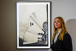 "© Licensed to London News Pictures. 26/02/2020. LONDON, UK. Artist Carolina Mazzolari poses with her work called ""Void"", 2019 (Starting price GBP3,000).  Preview of ""Human Touch"", an exhibition of one-of-a-kind artworks by international contemporary artists in collaborations with stitchers in British prisons.  In association with the charity Fine Cell Work, the artworks are on show at Sotheby's New Bond Street 26 February to 3 March 2020.  Photo credit: Stephen Chung/LNP"
