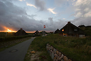 Hörnum. Sunset behind traditional reed-covered houses.