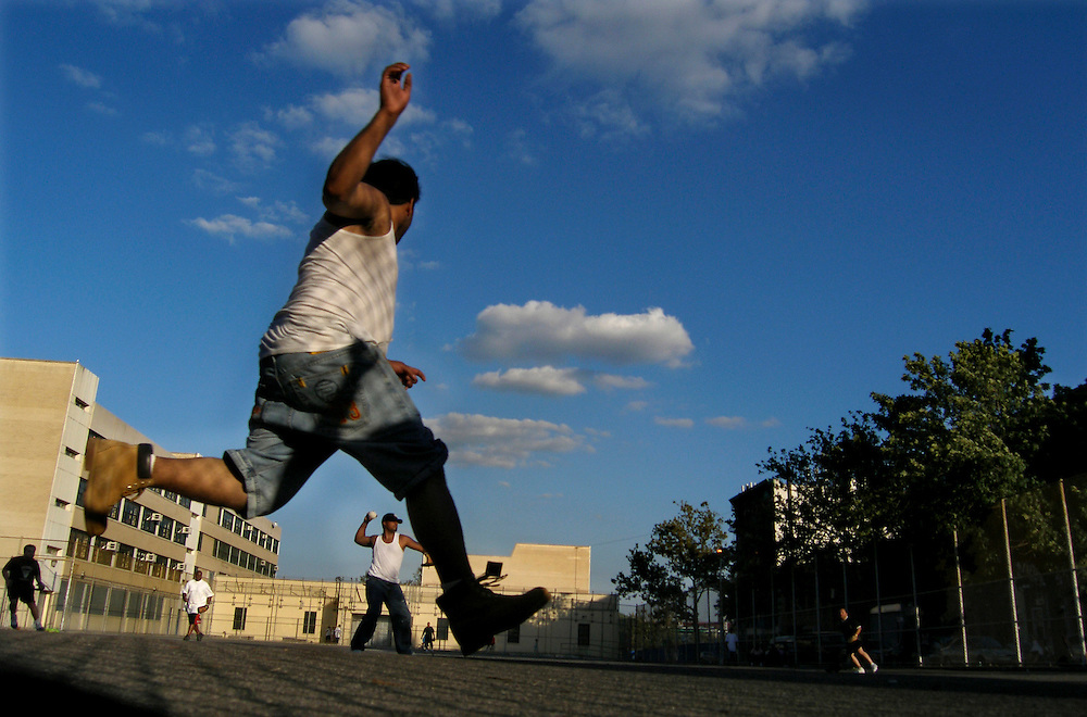A ballplayer rounds third base, watching the play of the field, during a Thursday afternoon softball game on the concrete playfield of a elementary school at E119th and Pleasant Avenues in Spanish Harlem, Summer 2005.
