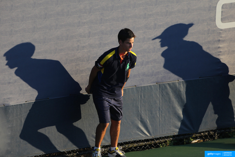 A ball boy and line judge cast shadows in the late afternoon sun on the outside courts during the US Open Tennis Tournament, Flushing, New York. USA. 28th August 2012. Photo Tim Clayton