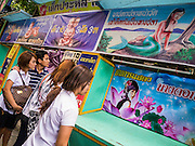 "27 NOVEMBER 2012 - BANGKOK, THAILAND:  Thai teenagers walk past the freak show tent at the Wat Saket Temple Fair in Bangkok. Wat Saket, popularly known as the Golden Mount or ""Phu Khao Thong,"" is one of the most popular and oldest Buddhist temples in Bangkok. It dates to the Ayutthaya period (roughly 1350-1767 AD) and was renovated extensively when the Siamese fled Ayutthaya and established their new capitol in Bangkok. The temple holds an annual fair in November, the week of the full moon. It's one of the most popular temple fairs in Bangkok. The fair draws people from across Bangkok and spills out in the streets around the temple.   PHOTO BY JACK KURTZ"