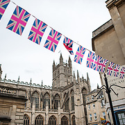 A string of Union Flag pennants runs across in the foreground, with Bath Abbey in the background in central Bath, Somerset, United Kingdom.
