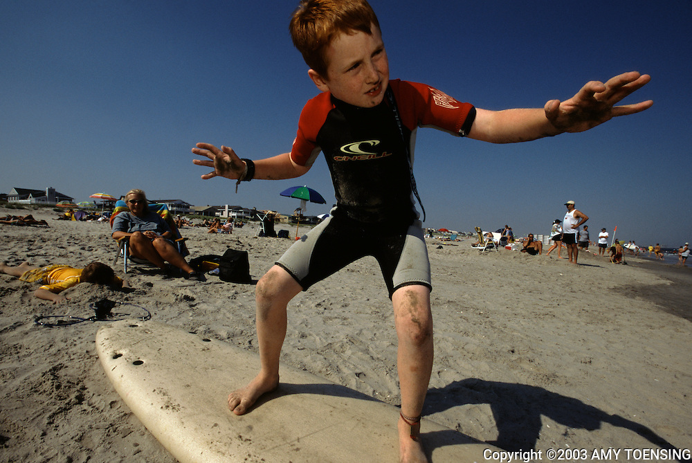 OCEAN CITY, NJ - MAY 25: A young boy practices balancing on a surfboard in preparation for a surfing class on the beach May 25, 2003 in Ocean City, New Jersey. The Jersey Shore, a 127 mile stretch of coastline known for its variety of beaches, boardwalks, small towns, natural beauty and summer crowds, has been a popular summer destination for over a century. (Photo By Amy Toensing)