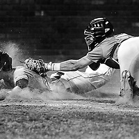 Elks' George Mendazona is tagged by North Sound's catcher Sam Finfer (13) as he attempts to score during the bottom of the 9th inning on Tuesday at Vince Genna Stadium. North Sound defeated the Elks 5-4 in nine innings.