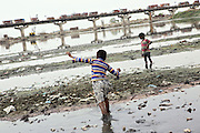 Two children are walking near the banks of the polluted Ganges River in Kanpur, Uttar Pradesh, near Jajmao Industrial Area. Sustaining life for thousands of years along the Indo-Gangetic plains, the river's ecosystem is in grave danger of being damaged beyond repair.
