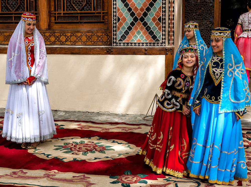 A group of folklore dancers at the Sheki Khan Palace prepare for their next performance, while the youngest performer steals the attention of tourists from the star of the show.