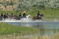Custers Last Stand Reenactment, Crow Indian Reservation, Montana, 7th Cavalry soldiers cross Little Bighorn River to attack Indian Camp.