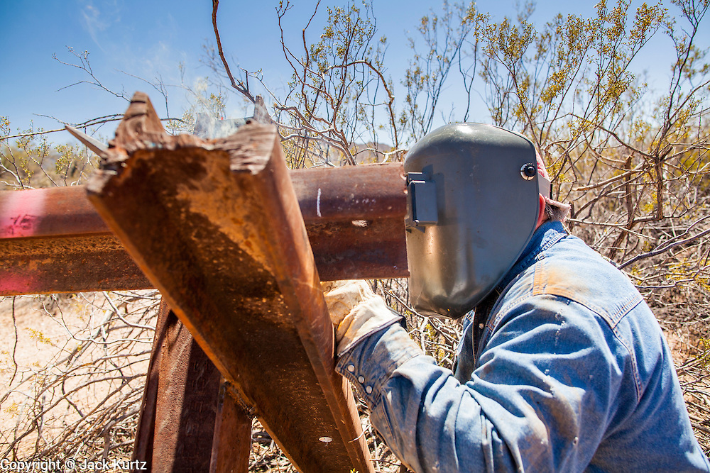 """03 MAY 2012 - VEKOL VALLEY, RURAL PINAL COUNTY, AZ:  Eric Reynolds (CQ), a BLM welder from the Safford office, works on vehicle barriers on Bureau of Land Management land south of Interstate 8 and west of Casa Grande in rural Pinal County. The area has been a hotbed of illegal immigrant and drug smuggling for years. The BLM has undertaken a series of """"surges"""" in the area, increasing their law enforcement patrols and partnering with Border Patrol and Pinal County Sheriff's Department officers to reduce criminal activity in the area.        PHOTO BY JACK KURTZ"""