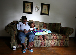 09 July 2006. New Orleans. Louisiana. <br /> Finding Faith. <br /> Faith Figueroa. A day in the life of. Faith sits with her mother Miriam as she sends a text message on her cell phone. <br /> Following a ten month search for the little girl whose face appeared on the Sept 19th, 2005 cover of Newsweek magazine, Faith's mother, Miriam Figueroa has returned to town with her three children. Faith, (1 yrs), Anfernya (5yrs) and Jacquelyn (13 yrs). <br /> Credit; Charlie Varley/varleypix.com