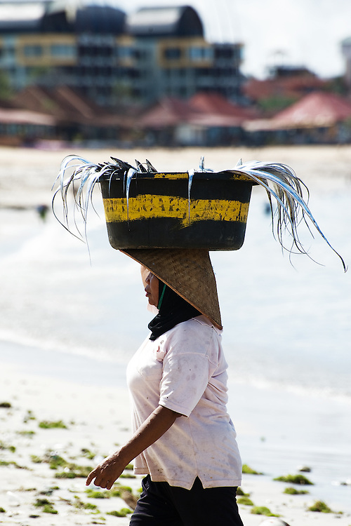 Female fishmonger with tray of fish on head