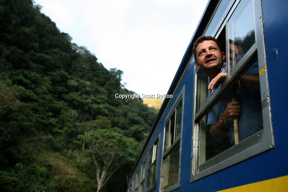 A tourist looks out the window of a train in route to Aguas Calientes, the stop where visitors get off to go see the Machu Picchu, in Peru on August 10, 2007. (Photo/Scott Dalton)