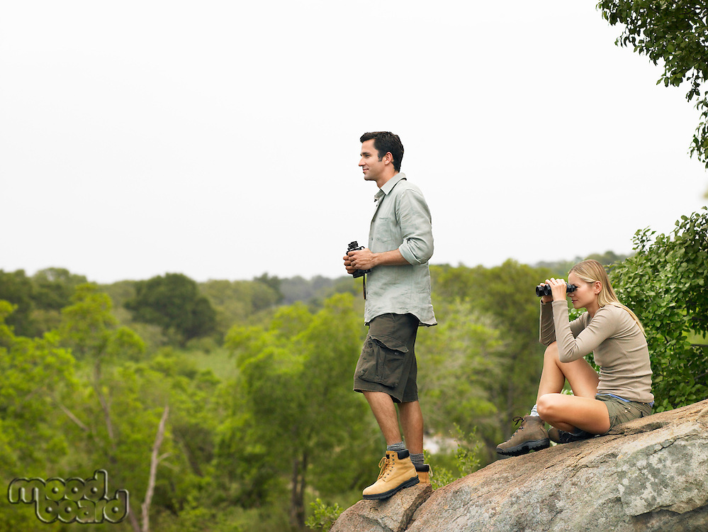 Man and woman on rock looking at view with binoculars