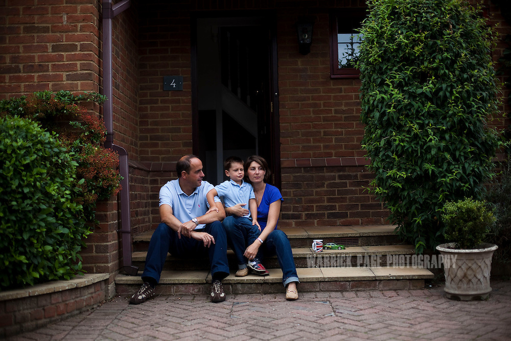 Julio and Eva Vildosola sit on the steps of their new home with their son Pablo, on September 1, 2012, in Buckden, England. The Spanish family immigrated to England due to the ongoing economic crisis that has impacted heavily on Spain. (Photo by Warrick Page)