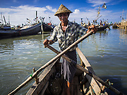 07 NOVEMBER 2014 - SITTWE, RAKHINE, MYANMAR: A boatman rows his lighter to shore bringing people back to a Rohingya IDP camp near Sittwe. The government of Myanmar has forced more than 140,000 Rohingya Muslims who used to live in Sittwe, Myanmar, into squalid Internal Displaced Person (IDP) camps. The forced relocation took place in 2012 after sectarian violence devastated Rohingya communities in Sittwe and left hundreds dead. None of the camps have electricity and some have been denied access to regular rations for nine months. Conditions for the Rohingya in the camps have fueled an exodus of Rohingya refugees to Malaysia and Thailand. Tens of thousands have put to sea in rickety boats hoping to land in Malaysia but sometimes landing in Thailand. The exodus has fueled the boat building boom on the waterfront near the camps. Authorities expect the pace of refugees fleeing Myanmar to accelerate during the cool season, December through February, when there are fewer storms in the Andaman Sea and Bay of Bengal.   PHOTO BY JACK KURTZ