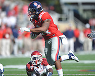 Ole Miss' Brandon Bolden (34) breaks through a tackle attempt by Arkansas safety Eric Bennett (14) at Vaught-Hemingway Stadium in Oxford, Miss. on Saturday, October 22, 2011. .