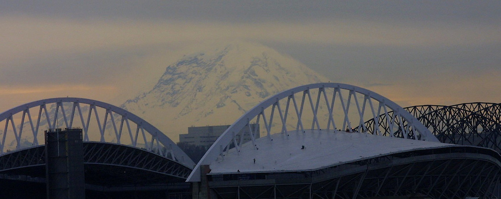 Mount Rainier is framed by the steel arches of the Seahawks stadium with the black roof members of Safeco Field, right. (Seattle Times staff photographer)
