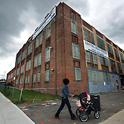 WASHINGTON, DC-OCT14: A woman pushes a stroller past Capital Self-Storage, October, 14, 2015, in Washington, DC. Many of the area homeless have possessions they want to keep safe, just nowhere permanent to live, so they store their belongings at Capital Self-Storage, where an upper-level unit costs $30/month. Some of the homeless patrons also spend their days in their storage units, when shelters are closed during midday hours. The storage facility near 3rd and Florida Avenue in Northeast, Washington, DC, is about to be replaced by a boutique hotel. (Photo by Evelyn Hockstein/For The Washington Post)