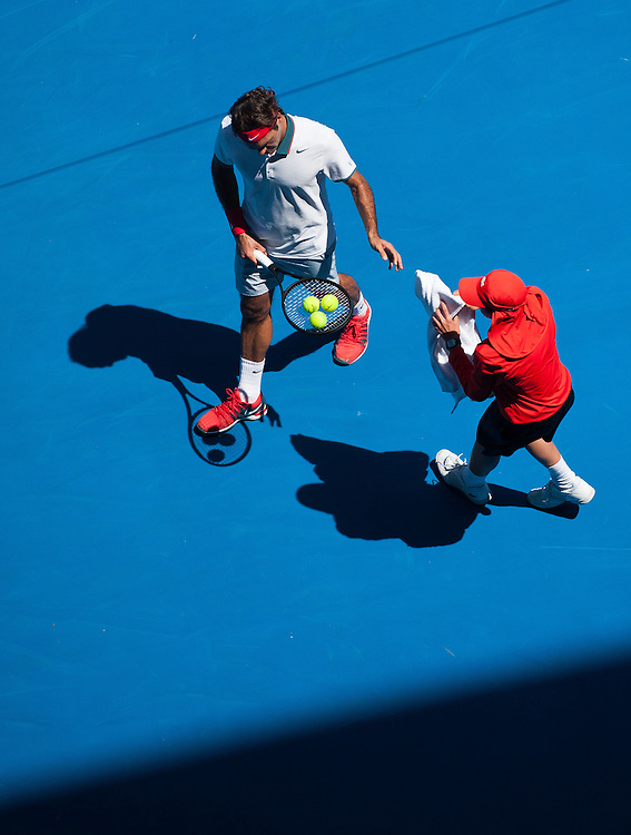 Roger Federer (SUI) takes a towel during a break in play in Day 2 of Australian Open play as temperatures soared to 43C, 109.4F . Federer beat J. Duckworth (AUS) 6-4, 6-4,6-2 in first round play of the 2014 Australian Open at Melbourne's Rod Laver Arena.
