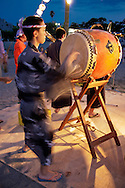 "Taiko Drummer participaing in summer O-bon festivities at Shonan Beach - Taiko means ""drum"" in Japanese and to the relatively recent art form of ensemble taiko drumming or more specifically ""kumi-daiko"".  Performances can last up to 25 minutes and typically follow a rapid/ sudden/urgent structure; the performance speeds up significantly towards the grand finale."