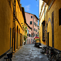Narrow Cobblestone Street in Lucca, Italy<br /> Lucca, Italy, was founded by the Etruscan civilization hundreds of years before Christ, but it was the Romans who gave it the rectangular street plan that has remained since 180 B.C. The thick defensive walls around this Tuscany town were added in the 16th century.  So, strolling along these narrow, cobblestone streets allows you to walk through Medieval and Renaissance history.