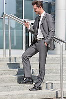 Full length of smiling businessman text messaging through cell phone while standing on steps outside office