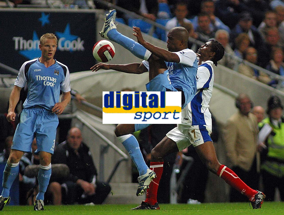 Photo: Paul Thomas.<br /> Manchester City v Portsmouth. The Barclays Premiership. 23/08/2006.<br /> <br /> Sylvian Distin (C) of Man City is pushed by Kanu (R) while Ben Thacther looks on.