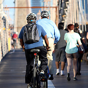 NEW YORK, SEPTEMBER 05: Pedestrians and tourists in Famous historic Brooklyn Bridge in Manhattan over Hudson River in September 05, 2013 in New York.