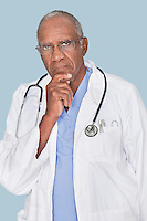 Portrait of a serious African American doctor with hand on chin over light blue background