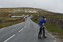 © Licensed to London News Pictures. 29/04/2016. Pateley Bridge, UK. A fan stops on his bike to take a photo at the summit of Greenhow Hill near Pateley Bridge in North Yorkshire. The steep climb which reaches 2.8km was the only climb during the opening stage of the 2016 Tour De Yorkshire. The three-day road cycling race held annually across Yorkshire is in it's second year. Photo credit : Ian Hinchliffe/LNP
