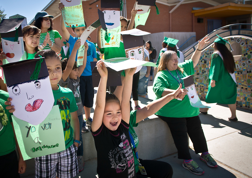 mkb051217a/metro/Marla Brose --  East San Jose Elementary students, including kindergartener Gloria Gallegos, center bottom, cheer on Albuquerque High graduates, while holding drawings of graduates in caps, Friday, May 12, 2017, in Albuquerque, N.M. The school's students cheered on a group of graduates as they walked around the school which was decorated with congratulations. The graduates are visiting other schools in their cluster to visit with young students and offer them a view of graduation. Albuquerque High School graduation ceremony will be Monday, May 15. (Marla Brose/Albuquerque Journal)