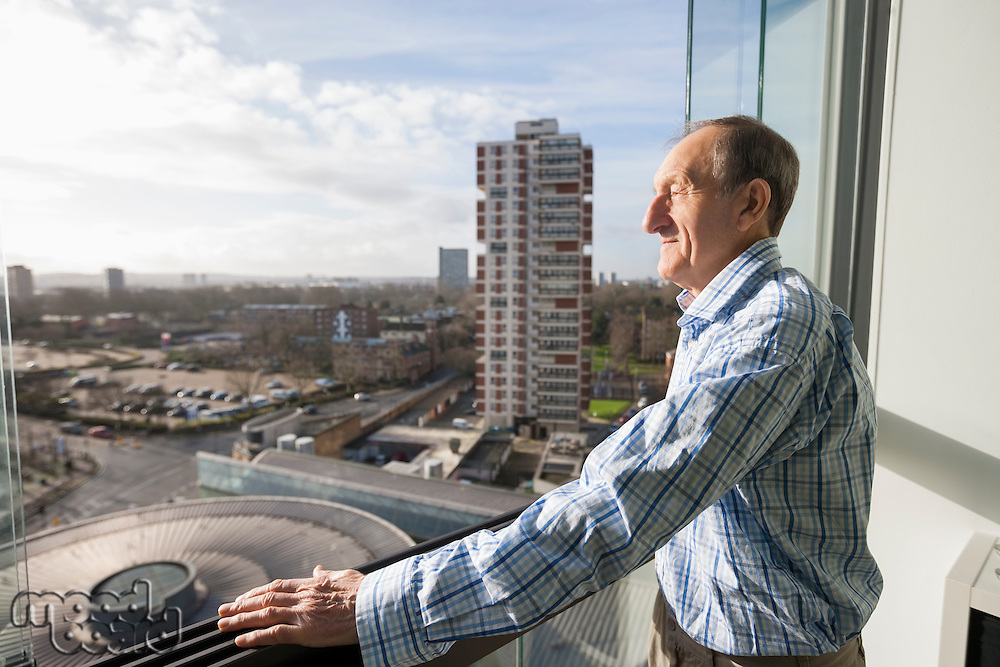 Side view of senior man standing on balcony