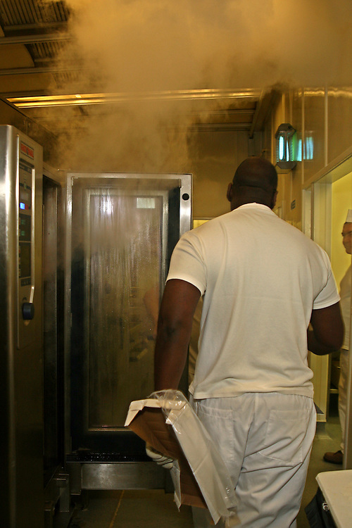 A prisoner walks past an oven in the busy kitchen of Coldingley prison..HMP Coldingley, Surrey was built in 1969 and is a Category C training prison. Coldingley is focused on the resettlement of prisoners and all prisoners must work a full working week within the prison. Its capacity is 390 prisoners.