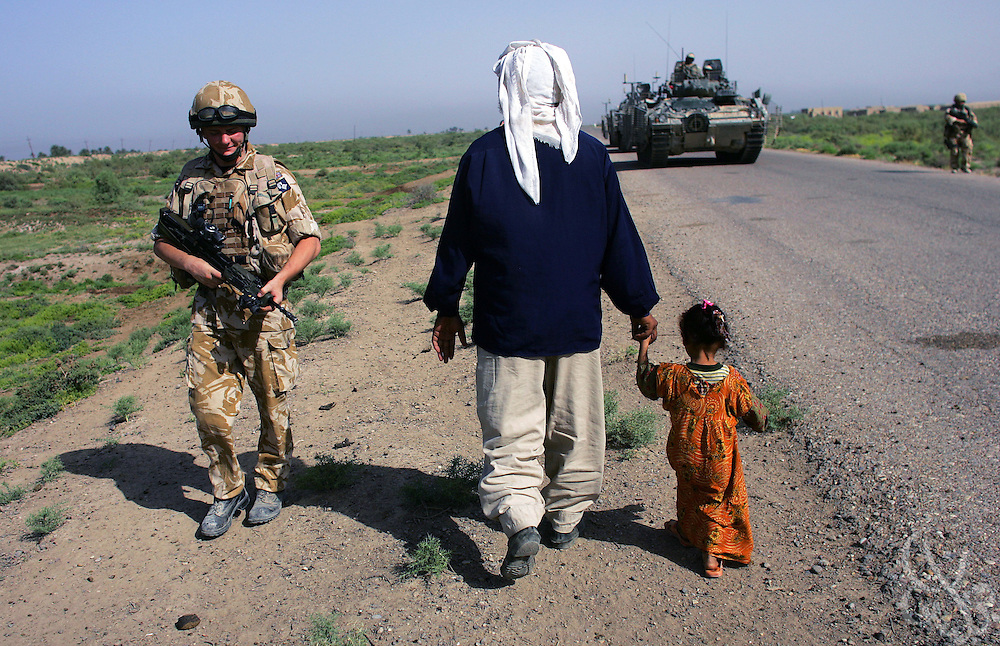 A soldier with the British Army's Queen's Royal Hussars battlegroup passes an Irai man walking with his daughter while on patrol near the town of al-Amarah, Iraq May 28, 2006.