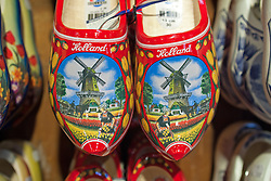 "Souvenir wooden shoes can be made to suit at a shop in Zaanse Schans, a popular day trip for Amsterdam visitors.  .From Wikipedia: "" Zaanse Schans is a neighbourhood of Zaandam, near Zaandijk in the municipality of Zaanstad in the Netherlands, in the province of North Holland. It has a collection of well-preserved historic windmills and houses; the ca. 35 houses from all over the Zaanstreek were moved to the museum area in the 1970s. The Zaans Museum, established in 1994, is located in the Zaanse Schans..The Zaanse Schans is one of the popular tourist attractions of the region and an anchor point of ERIH, the European Route of Industrial Heritage. The neighbourhood attracts approximately 900,000 visitors every year..The windmills were built after 1574."".Also from Wikipedia: "" Along the river Zaan, you can find still dozens of original windmills (mostly entirely made of wood), still technically functioning, some of them over 350 years old. Next to these there are many 19th century stone industrial buildings, nowadays derelict or converted into apartments, but still recognisable as industrial buildings.""."