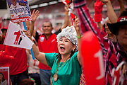 01 JULY 2011 - BANGKOK, THAILAND:   A woman cheers for Pheua Thai parliamentary candidates during a Pheua Thai rally in Bangkok Friday. Thailand's divisive election campaign drew to a close Friday in Bangkok. Most of the parties had large rallies in an effort to sway last minute undecided voters. Pheua Thai, the party of ousted Prime Minister Thaksin Shinawatra held a massive rally in Rajamakala Stadium (also called Ramkamhaeng Stadium) to close out their campaign. A monsoon thunderstorm didn't keep people away from the event. Most Thai public opinion polls show Pheua Thai with a healthy lead over their arch rivals (and incumbent party in power) the Democrats. Thaksin's youngest sister, Yingluck Shinawatra, is running for Prime Minister under the Pheua Thai banner. If elected, she will be Thailand's first female Prime Minister.     PHOTO BY JACK KURTZ