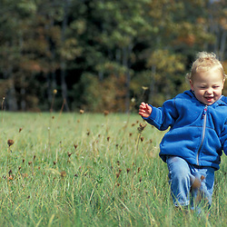 Kennebunkport, ME.. A baby boy enjoys a fall day in a field on the Steele Farm. Fall.