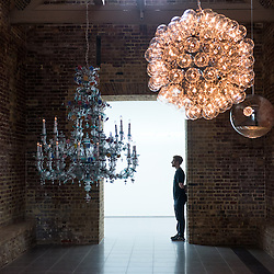 London, UK - 15 September 2014: A member of the staff stands near pendant lamps by Cerith Wyn Evans including 'Taraxacum 2014' (Center, illuminated) during the press preview of his new solo exhibition at Serpentine Sackler Gallery.