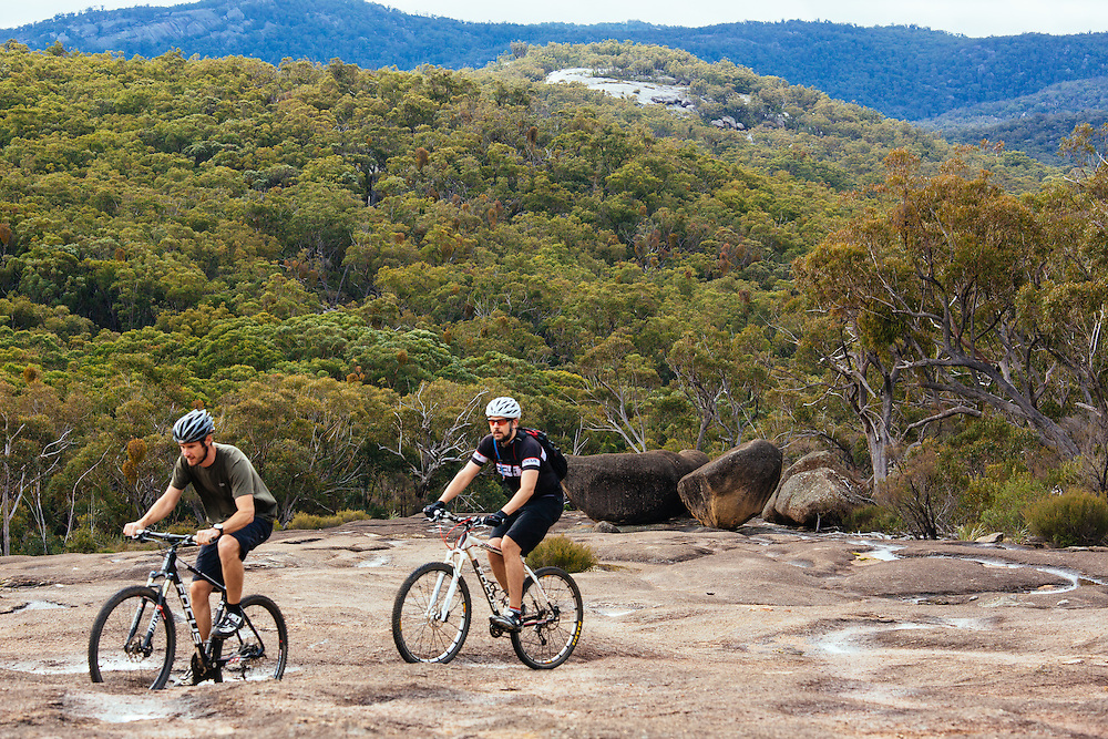 Mountain bike riders going up the wide granite slabs along the Peak Trail in Girraween National Park.