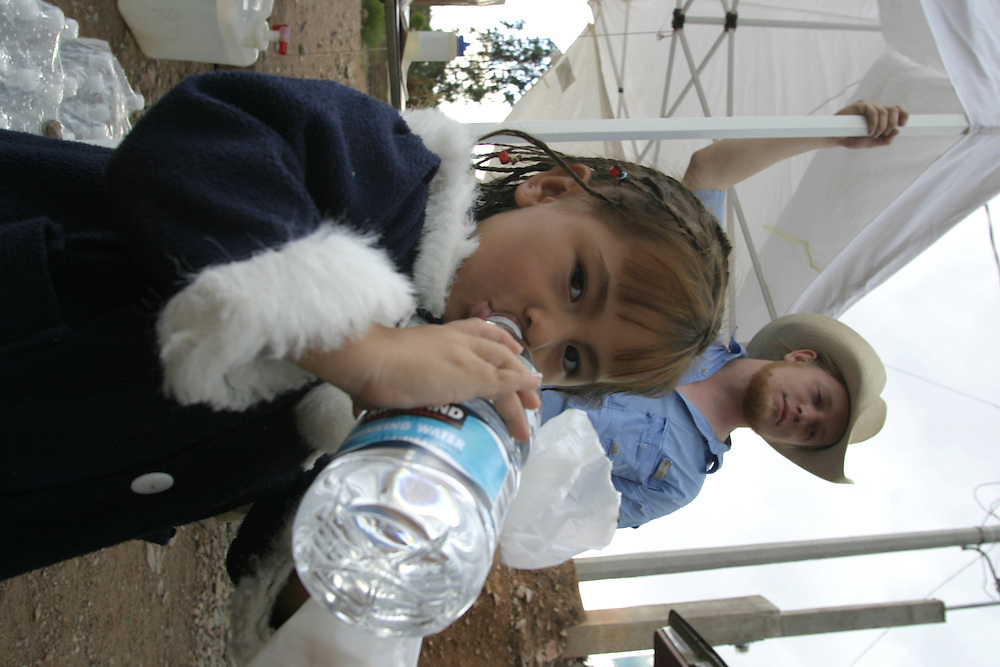Three-year-old Atiziry Briseo receives water from volunteers with the No More Deaths humanitarian group on the Mexican side of the border town of Nogales on 14 July 2006 after failing to cross into the US with her mother. The mother and child wandered the desert in Arizona for three days before being caught by American border patrol.....